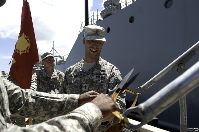 Chief Warrant Officer 3 Thomas Barnes, commander 163rd Transportation Detachment, 524th Combat Sustainment Support Battalion, 45th Sustainment Brigade, cuts a ribbon as the unit assumes responsibility of the Logistical Support Vessel Lt. Gen. William B. Bunker at Joint Base Hickam Pearl Harbor, Hawaii, June 29, 2012.