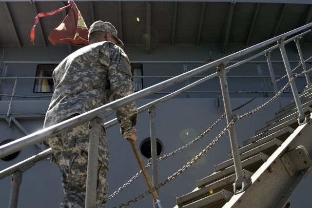 The guidon bearer from the 163rd Transportation Detachment, 524th Combat Sustainment Support Battalion, 45th Sustainment Brigade, races the unit's guidon onto the Logistical Support Vessel Lt. Gen. William B. Bunker as the unit takes responsibility of the ship at Joint Base Hickam Pearl Harbor, Hawaii, June 29, 2012.