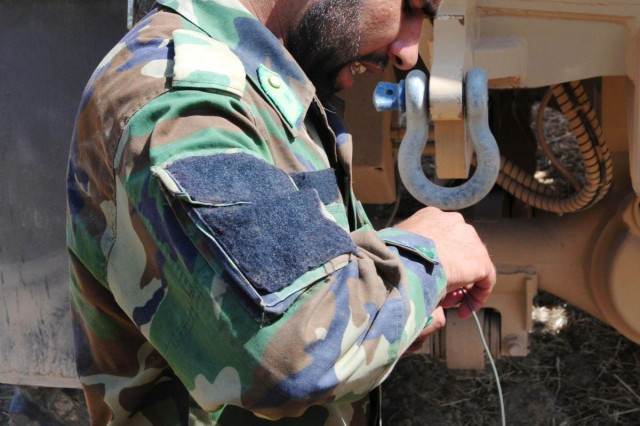 Afghan National Army 1st Lt. Ismatullah, with Route Clearance Company, 4th Brigade, 205th Corps, connects detonation cord to an igniter while being supervised by his coalition counterpart during a route clearance mission in Uruzgan province, Afghanistan, July 7, 2012.