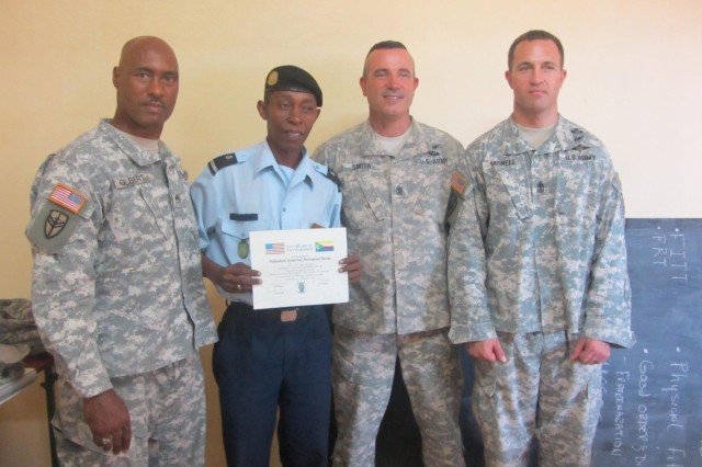Staff Sgt. David Gilbert (left), squad leader, 1st Sgt. Louis Smith (second from right), mission commander, and 1st Sgt. Paul Yarnell (right), first sergeant, all with the 3rd Squadron, 124th Cavalry Regiment, Texas National Guard, assigned to the Combined Joint Task Force -- Horn of Africa, pose with Comorian Army Adjudant Youssouf Mohamed Boina, operations NCO for the Comorian Army of National Development at the completion of a five-day noncommissioned officer development seminar at the National School of Army and Gendarmerie, held June 12-16, 2012. Noncommissioned officers from the U.S. and Comorian armies partnered together to share best practices of basic NCO skills.