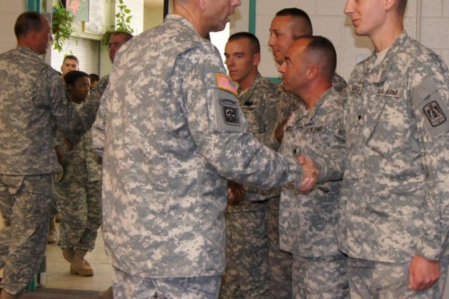 Col. Patrick Dedham, commander, 11th Tactical Theater Signal Brigade (left), congratulates Spc. Joel Glover and gives him a coin for his efforts during his recent deployment to Honduras.