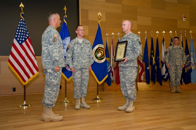 Col. Ed Swanson, project manager for Warfighter Information Network-Tactical (WIN-T) (center), passed the WIN-T Increment 3 charter from Lt. Col. Robert Collins, continuing product manager (PdM) of WIN-T Increment 2 and outgoing PdM of WIN-T Increment 3 (left), to Lt. Col. Joseph W. Roberts, incoming PdM  for WIN-T Increment 3 (right). The change of charter ceremony was held at the Myer Auditorium in Aberdeen Proving Ground, Md. on June 29, 2012.