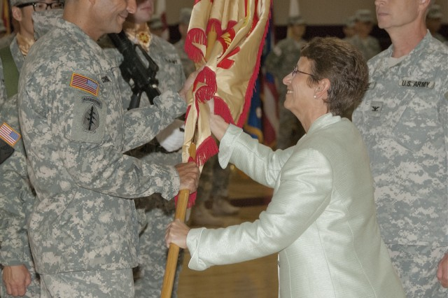 Col. Darin S. Conkright (left) assumes duties as the United States Army Garrison Humphreys Commander, taking the guidon from Debra D. Zedalis, Pacific Region Director for Installation Management Command, during a ceremony July 11.