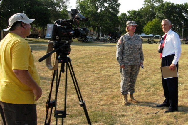 Maj. Gen. Patricia E. McQuistion, commanding general of Army Sustainment Command, responds to WHBF-TV channel 4 co-anchor Steve Long, during a live remote July 6 as the Golden Knights circle overhead before parachuting to Rock Island Arsenal. (Photo by Dan Carlson, ASC Public Affairs)