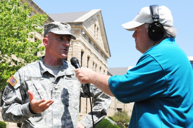 Col. Scott J. Lofreddo, chief of staff, Army Sustainment Command, responds to questions from WLLR-FM 103.7 radio personality Pat Leuck the morning of July 7. Senior leaders throughout the various Rock Island Arsenal's commands participated in live broadcasts to help promote the 150th anniversary. (Photo by Jon Connor, ASC Public Affairs)