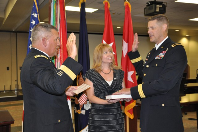 "FORT BRAGG, N.C. (July 11, 2012)  As Andree O'Connor looks on, Lt. Gen. Raymond V. Mason, the U.S. Army's deputy chief of staff for Logistics, administers the Oath of Office to newly promoted Maj. Gen. John R. ""Jack"" O'Connor, U.S. Army Forces Command's deputy chief of staff-G4 (Logistics). Mason, who is now the Army's senior logistician, was O'Connor's predecessor at FORSCOM."