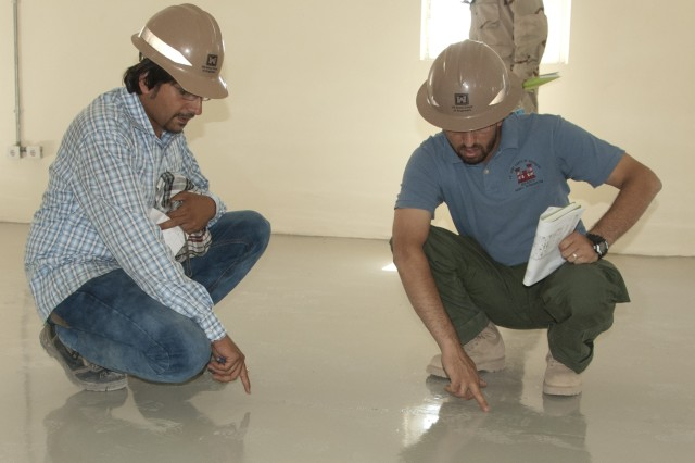 Eraj Akbarpoor, Afghan quality assurance representative, (left) and Tariq Taheri, Afghan project engineer, inspect a floor in one of several buildings nearing completion on the 9th Commando compound in Herat, Afghanistan, July 2, 2012.