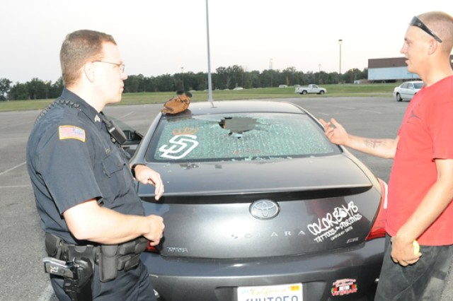 Spc. Chase Kieffe, Headquarters, Headquarters Company, 1st Engineer Brigade (right), describes finding his friend's vehicle with a smashed back window and softball in the backseat to Jason Miketish, civilian police sergeant, June 25 near a baseball diamond on post.