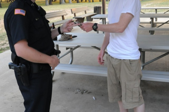 Officer Jason Miketish, civilian police sergeant, checks Brandon Siliano's ID card to verify his drinking age at a park on post during the evening patrol.