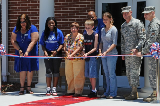This scene was taken moments before a ribbon was cut to celebrate the opening of the Youth Activities Center on Mindoro Loop. From left are Dagmar Peguero-Olinger; Lyrick Dent; Linda Heifferon, Gavin Thigpen; Hannah Tate; Col. Milton; and Garrison Command Sgt. Maj. Felicioni.  Gary Williams is behind Gavin Thigpen.