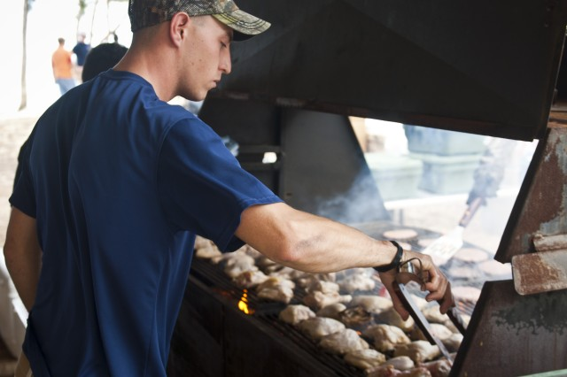 Sgt. Dan Cortez, orderly room sergeant for Headquarters and Headquarters Company, 8th Special Troops Battalion, 8th Theater Sustainment Command, turns barbeque chicken at the company's organizational day at Bellows Air Force Base, July 6.