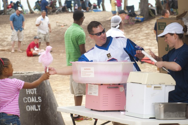 1st Lt. Nicolas Roth, executive officer for Headquarters Company, 8th Special Troops Battalion, 8th Theater Sustainment Command, hands off some cotton candy during the company's organizational day at Bellows Air Force Base, July 6.