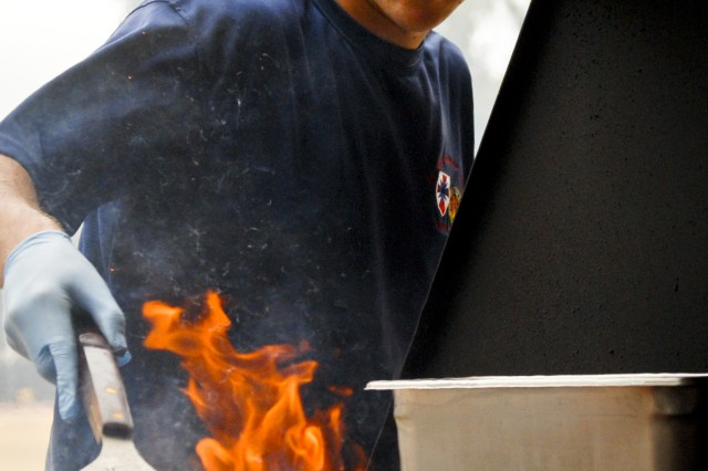 Staff Sgt. James Yancis, intelligence analyst for the 8th Theater Sustainment Command, helps work the grill during the company's organizational day at Bellows Air Force Base, July 6.