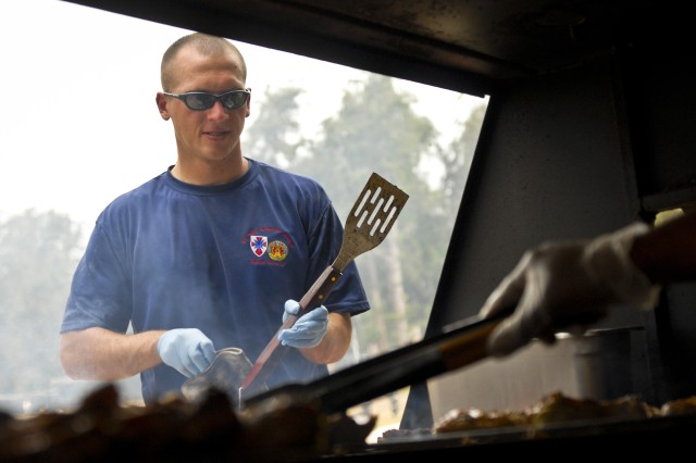 Staff Sgt. James Yantis, intelligence analyst for the 8th Theater Sustainment Command, helps work the grill during the company's organizational day at Bellows Air Force Base, July 6.