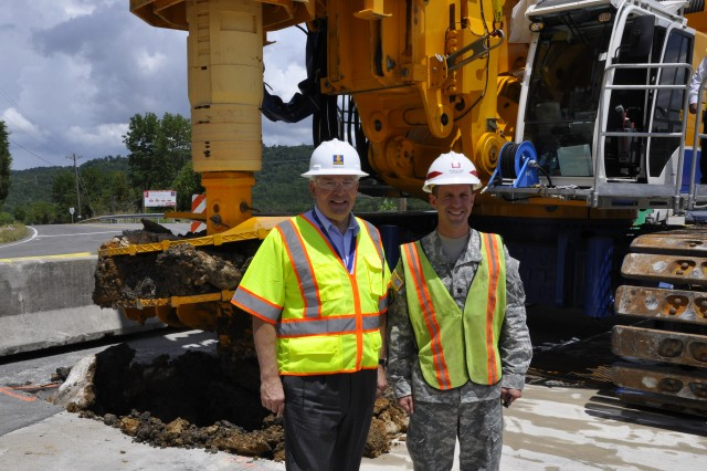Lt. Col. James A. DeLapp, U.S. Army Corps of Engineers Nashville District commander (Right), and Professor Thomas Bauer, chief executive officer for the Bauer Group, pose in front of a drill rig July 11, 2012 that made the first excavation in the earthen portion of Center Hill Dam to install a concrete barrier wall. The $106 million project is scheduled for completion in late 2015. (USACE photo by Fred Tucker)