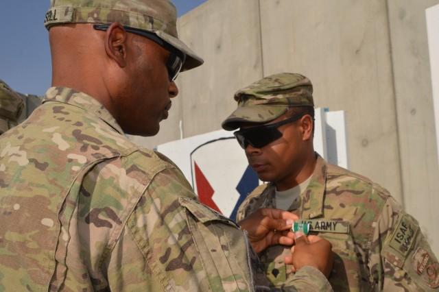 """Col. Michel M. Russell, Sr., 401st Army Field Support Brigade commander presents an Army Commendation Medal with the """"V"""" device to Spc. David P. Clark in recognition of his actions when his base came under enemy attack Jun. 1. Clark was also awarded a Combat Action Badge.  Clark is with the 27th Infantry Brigade Combat Team, a New York National Guard unit , and is temporarily assinged to the 401st as a customs agent."""