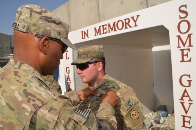 Col. Michel M. Russell, Sr., 401st Army Field Support Brigade commander presents a Combat Action Badge to 1st Lt. Eric J. Leon in recognition of his actions when his base came under enemy attack Jun. 1. Leon is a member of the 27th Infantry Brigade Combat Team, a New York National Guard unit and is temporarily assigned to the 401st as an Redistribution Property Assistance Team officer-in-charge.