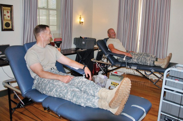 Fort Riley Garrison Commander William Clark, left, and Sgt. Jared Ellis, HHC, USAG, right, prepare to donate blood June 27 at Grimes Hall.