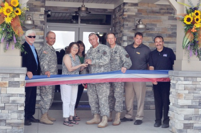 Fort Riley officials cut a ribbon July 2 signifying the opening of the Ellis Heights Neighborhood Center on Custer Hill. Pictured from left to right are Mick McCallister, RCI-Housing Manager; Fort Riley Command Sgt. Maj. Miguel Rivera; Rhonda Bartlett, Ellis Heights resident; Andrea Clark, wife of Garrison Commander Col. William Clark; DES Sgt. Maj. Ancel Bartlett, Ellis Heights resident; Garrison Commander Col. William Clark; Scott Kotwas, director of construction, Picerne Military Housing; and Shawn Cheever, project manager, Picerne Military Housing.