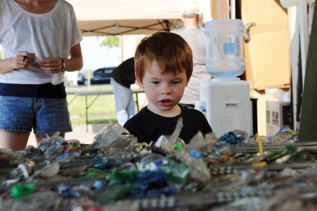 Alexander Kocsis, 4, tries to figure out the weight of a bale of recycled bottles, which weighed about 1,800 pounds, for a contest during the Fort Riley Recycling Center's open house, which coincided with a USO Fort Riley No Dough Dinner June 28 at Fort Riley, Kan.