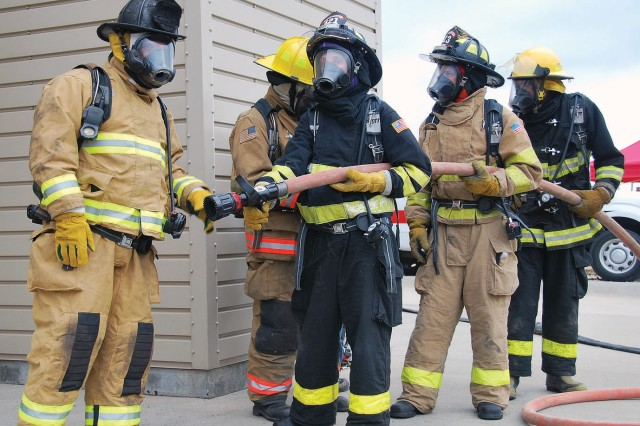 Firefighters from departments throughout the CFHR prepare to enter a training tower July 8 at Camp Funston as part of the fire streams and hose practices class offered during the KSFFA Regional Fire School, a two-day training event hosted by FES at Fort Riley, Kan.