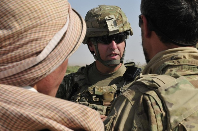 Maj. Roger Shaw, an officer with the 3rd Stryker Brigade Combat Team, 2nd Infantry Division, listens to members of the local Afghan Border Police at a checkpoint during Operation Buffalo Thunder II near Baradge Kotal, Afghanistan, June 29, 2012. During the eight-day mission, Afghan and American forces cleared more than 120 kilometers of rugged terrain and escorted approximately 60 truckloads of humanitarian aid for distribution to the people of Shorabak.
