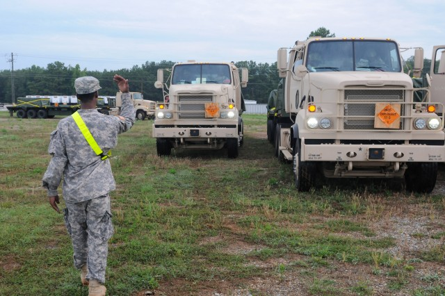 Pvt. Earnest L. Tart, transportation and logistics specialist from Fayetteville, N.C., assigned to the 216th Movement Control Team (Task Force Hellcat), directs truck drivers from the 432nd Transportation Company to a staging area before conducting inspections to ensure the convoy is ready to make its 500-mile trek from Anniston Army Depot, Ala., to Crane Army Ammunition Activity in Crane, Ind., as part of Operation Golden Cargo 2012.