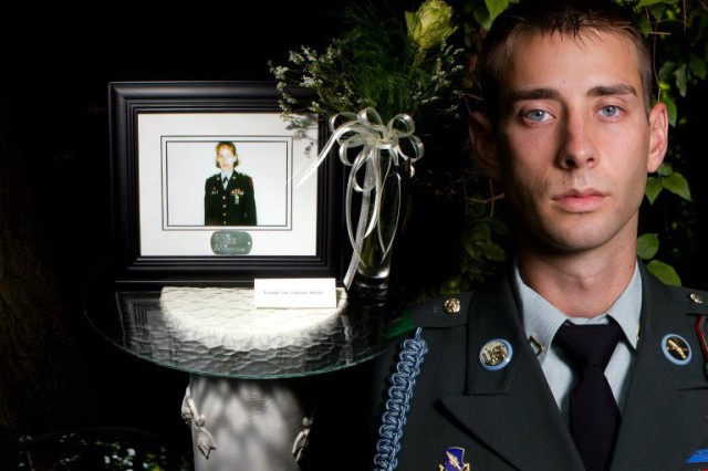 U.S. Army Sgt. Colton Hurley, an infantry team leader with the 82nd Airborne Division's 1st Brigade Combat Team, stands next to a memorial for his mother, Sgt. Krystal Hurley, in this undated photograph.  Hurley was inspired to serve 20 years in the Army by his mother, a combat medic who passed away when he was an infant. (U.S. Army photo by Sgt. Michael J. MacLeod, Task Force 1-82 PAO)