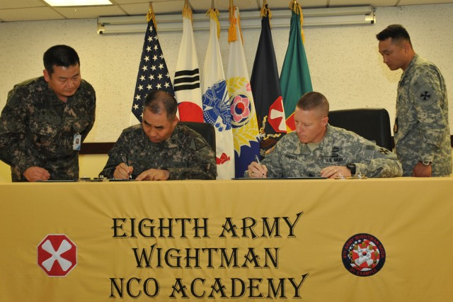 Republic of Korea Army Sergeant Major of the Army Jeong Hae-cheon (left) and Eighth Army Command Sgt. Maj. Rodney D. Harris sign a memorandum of understanding July 16, 2012, to establish a combined training program at the Eighth Army Wightman Noncommissioned Officer Academy.