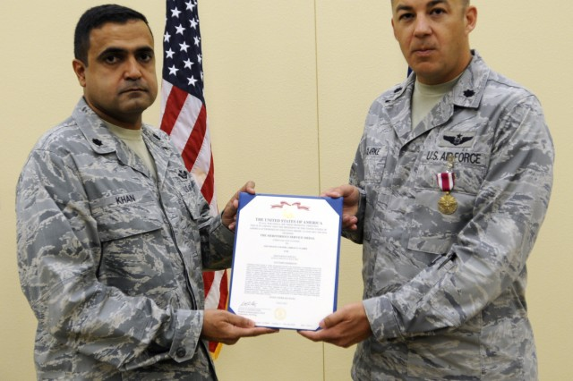 """EL PASO, Texas """" U.S. Air Force Lt. Col. Haider A. Khan, (left), deputy commander for the 3rd Air Support Operations Squadron, based out of Fort Hood, Texas, presents the Meritorious Service Medal to Air Force Lt. Col. Adrian N. Clarke, outgoing commander for the 7th ASoS, during a change of command ceremony held at Fort Bliss, Texas, July 13, 2012. Clarke is a native of Las Cruces, N.M., and has been the commander of the 7th ASoS for the last two years. (U.S. Army photo by Sgt. Richard Andrade, 16th Mobile Public Affairs Detachment)"""