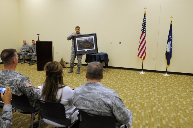 """EL PASO, Texas """" U.S. Air Force Lt. Col. Adrian N. Clarke, outgoing commander for the 7th Air Support Operations Squadron, displays a personalized frame to the 7th ASoS during a change of command ceremony held at Fort Bliss, Texas, July 13, 2012. Clarke is a native of Las Cruces, N.M., and has been commander of the 7th ASoS """"Hustlers,"""" since July 2010. (U.S. Army photo by Sgt. Richard Andrade, 16th Mobile Public Affairs Detachment)"""