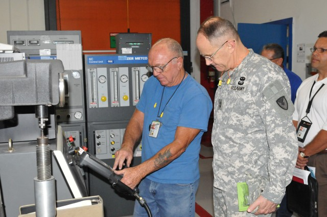 A Corpus Christi Army Depot robotic metal spray operator shows the robot in action to Maj. Gen. Frank Turner III, commanding general of the U.S. Army Security Assistance Command.