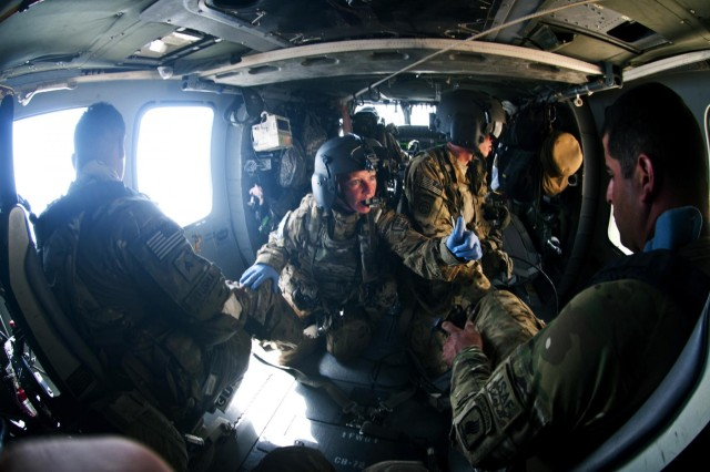 Staff Sgt. Erin Gibson, 31, of Covington, Ohio, reassures patients in the back of an 82nd Combat Aviation Brigade medevac helicopter while Spc. Bryan Heaston, 30, of Lusby, Md., maintains a close watch on security and safety in Logar province, Afghanistan, July 8, 2012.