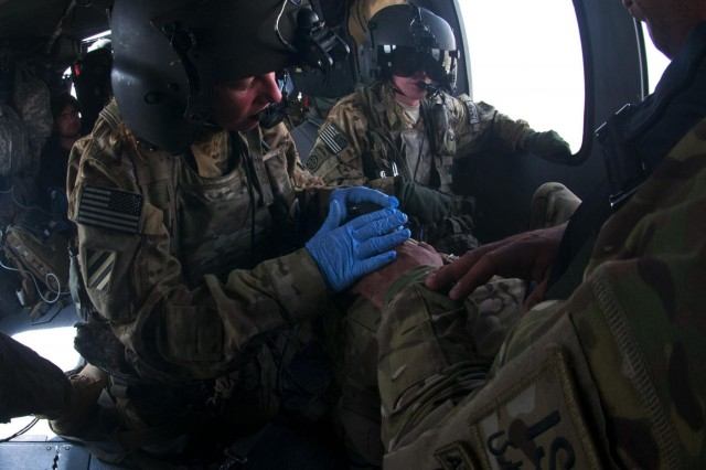 Staff Sgt. Erin Gibson, 31, of Covington, Ohio, treats a patient in the back of an 82nd Combat Aviation Brigade medevac helicopter while Spc. Bryan Heaston, 30, of Lusby, Md., maintains a close watch on security and safety in Logar province, Afghanistan, July 8, 2012.