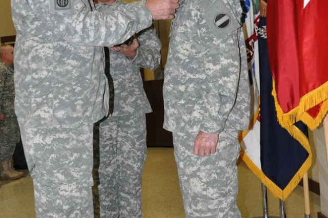 FORT BRAGG, N.C. -- The FORSCOM commanding general, Gen. David M. Rodriguez (Ieft), presents Lt. Gen. Howard B. Bromberg with a Distinguished Service Medal as Bromberg's enlisted aide, Sgt. Casey Manahan, observes.
