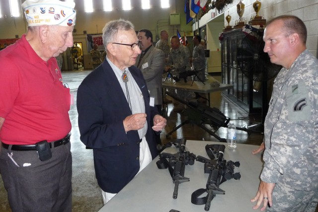 "New York Army National Guard Master Sgt. Troy Haley demonstrates modern M-4 rifles to World War II veterans James ""Pete"" Pettus and Dee Eberhart during a visit of 42nd Infantry Division veterans to the modern day headquarters of the 42nd Infantry Divisions, July 14, 2012. The Rainbow Division Veterans Memorial Foundation held its annual reunion in Albany so that members of the present division headquarters could participate."