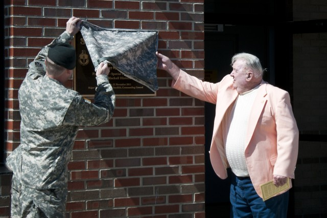 Lt. Col. George M. Bond (left) and Bud O'Connell unveil the dedication plaque for Stevens Hall during a ceremony recognizing the building's namesake, Lowell Stevens, May 10 on Camp Mackall. (U.S. Army photo by Dave Chace, SWCS Public Affairs Office)