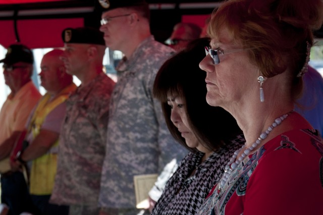 "Family of the late Lowell Stevens, including his wife (center) stand in silence as the Soldiers of 1st Battalion, 1st Special Warfare Training Group (Airborne) play ""The Ballad of the Green Beret"" in honor of Stevens during a dedication ceremony May 10 on Camp Mackall. Stevens, a Vietnam veteran and Special Forces noncommissioned officer, retired from active-duty in 1980 and spent 23 more years as a Fort Bragg civilian range control official at Camp Mackall. (U.S. Army photo by Dave Chace, SWCS Public Affairs Office)"