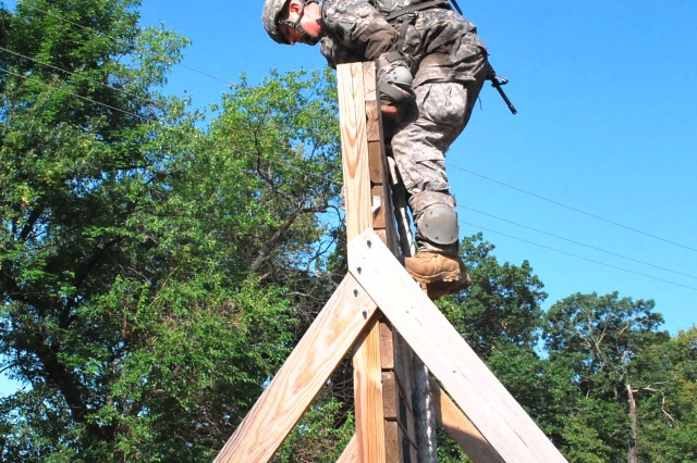 Staff Sgt. Jeremiah Scheil, Army Contracting Command, Fort Wainwright, Alaska, successfully scales a wall July 17. The last day of the Army Materiel Command's Best Warrior Competition, held at Rock Island Arsenal, Ill., is July 18. (Photo by Jon Connor, ASC Public Affairs)