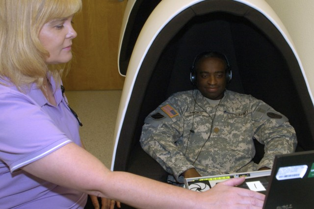 """Michelle Fielder, WTB occupational therapy supervisor, the essential goal of occupational therapy is for a Soldier to learn to be independent and comfortable in their environment whether it is home, work or school. One of the memory improvement tools used to help WTB Soldiers like Maj. Rontario Hicks is the """"egg module."""" (Photo by Gloria Montgomery, WTB PAO)"""