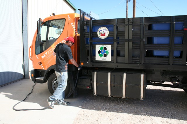 Ryan Sullivan, Directorate of Public Works recycle operator, charges the Recycle Program's new all-electric truck.
