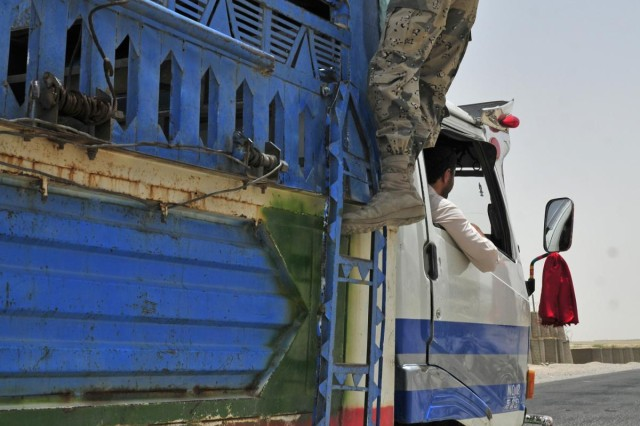 A member of the Afghan Border Police at Checkpoint 9 inspects in back of a jingle truck along Highway 4 in the district of Spin Boldak, Afghanistan, July 5, 2012. This Afghan Border Police checkpoint is one of the few that operates 24/7.