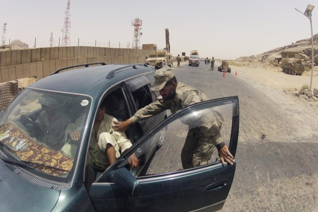 A member of the Afghan Border Police prevents a civilian from exiting his vehicle during a search at Checkpoint 9 along Highway 4 in the district of Spin Boldak, Afghanistan, July 5, 2012. This Afghan Border Police checkpoint is one of the few that operates 24/7.
