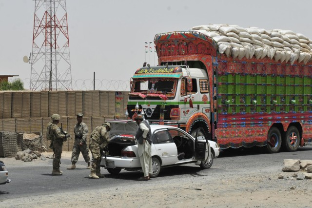 An Afghan Border Policeman and members of Alpha Company, 1st Battalion, 17th Infantry Regiment, 2nd Infantry Division, conduct traffic control point operations at Checkpoint 9 along Highway 4 in the district of Spin Boldak, Afghanistan, July 5, 2012. This ABP checkpoint is one of the few that operates 24/7.