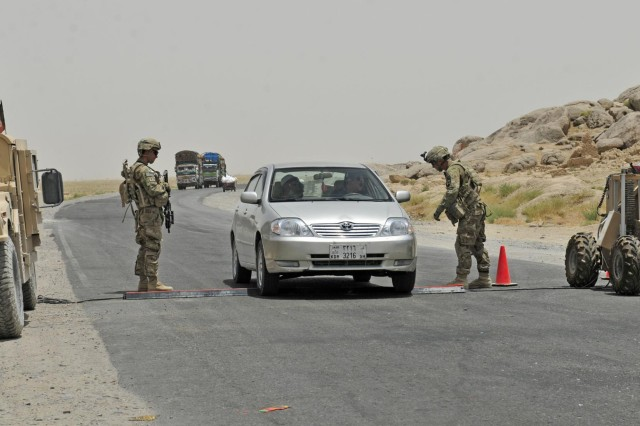 Sgt. Joseph Barrow and Spc. Anthony Saenz, members of Alpha Company, 1st Battalion, 17th Infantry Regiment, 2nd Infantry Division, conduct traffic control operations at Checkpoint 9 along Highway 4 in the district of Spin Boldak, Afghanistan, July 5, 2012. This Afghan Border Police checkpoint is one of the few that operates 24/7.