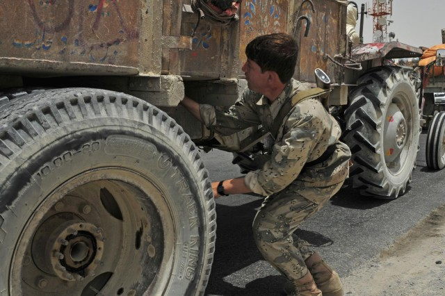 A member of the Afghan Border Police searches for contraband during vehicle inspections at Checkpoint 9 along Highway 4 in the district of Spin Boldak, Afghanistan, July 5, 2012. This Afghan Border Police checkpoint is one of the few that operates 24/7.