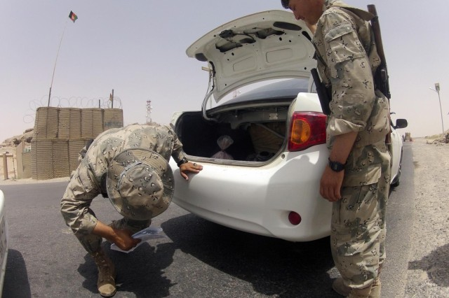 Members of the Afghan Border Police conduct an inspection of a vehicle at Checkpoint 9 along Highway 4 in the district of Spin Boldak, Afghanistan, July 5, 2012. This Afghan Border Police checkpoint is one of the few that operates 24/7.