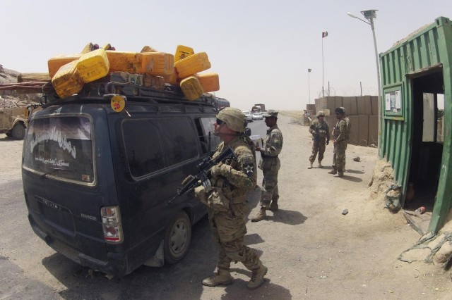 Staff Sgt. Joshua Fairchild, Alpha Company, 1st Battalion, 17th Infantry Regiment, 2nd Infantry Division, works with members of the Afghan Border Police at Checkpoint 9 along Highway 4 in the district of Spin Boldak, Afghanistan, July 5, 2012. This Afghan Border Police checkpoint is one of the few that operates 24/7.