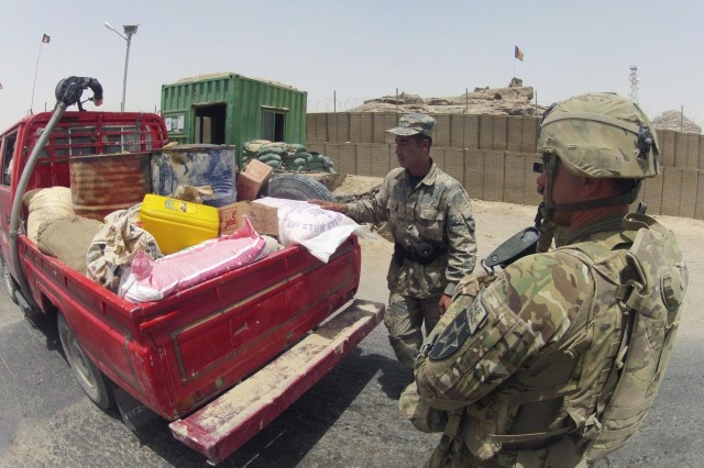 A member of the Afghan Border Police searches a pickup truck at Checkpoint 9 along Highway 4 in the district of Spin Boldak, Afghanistan, July 5, 2012. This Afghan Border Police checkpoint is one of the few that operates 24/7.