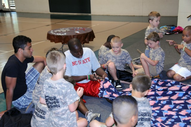 Military and non-military children staying at the YMCA Camp Hanes in King, N.C.help to make blankets during Military Day activities on July 11 which will later be distributed to families of fallen Soldiers. The week-long camp included the Military Day where children were exposed to different aspects of military life such as, Army heater meals, camoflauge face paint, physical training and a static vehicle display. The children also wrote supportive letters to veterans and drew pictures that will become parts of a larger mural as a part of Project S.N.A.P. and the Operation Grateful Nation Mosaic Mural project.